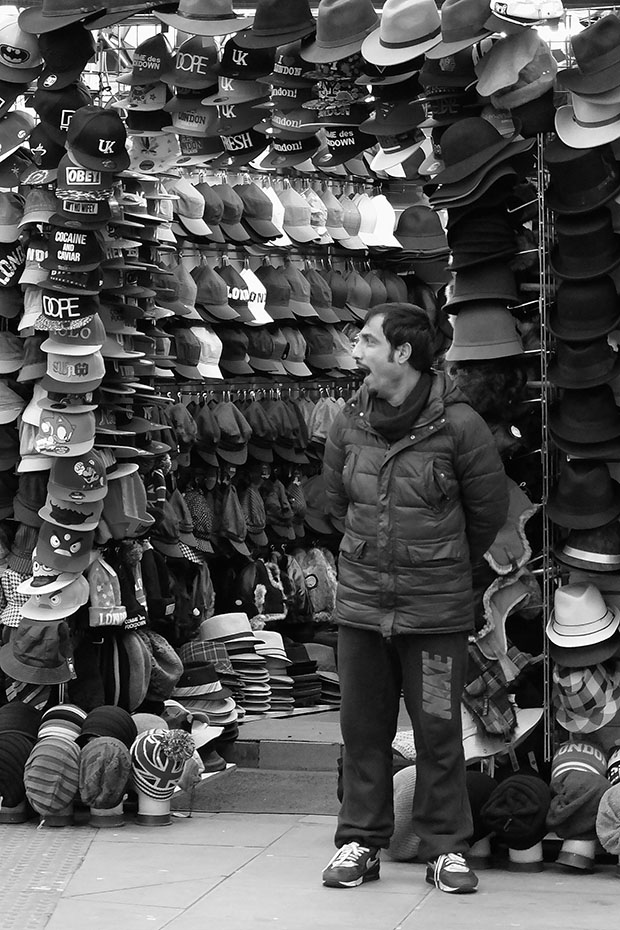 © Neil Turner, January 2014. Bored shop keeper outside his open hat shop just outside one of main areas of Camden Market