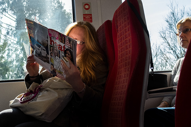 March 2014. Passenger on the train between Bournemouth and London Waterloo reading HEAT magazine as the train passes through Woking. ©Neil Turner