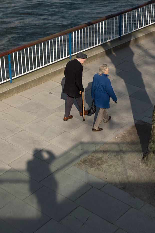 ©Neil Turner, March 2014. The photographer's shadow forms part of the scene as an elderly couple walk along South Bank of the River Thames in London.