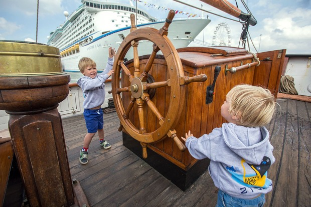 """The sons of the late Olympian Andrew """"Bart"""" Simpson at the helm of the tall ship PHOENIX alongside Europe's largest temporary marina. ©Neil Turner, September 2014."""