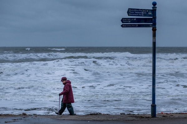 ©Neil Turner, November 2014. A pensioner walks along the beach near Bournemouth Pier.