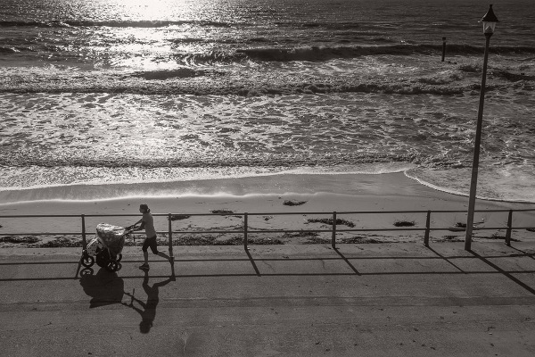 ©Neil Turner, November 2014. A young woman jogs along the promenade near Portman Ravine in Bournemouth with a child in a pushchair.
