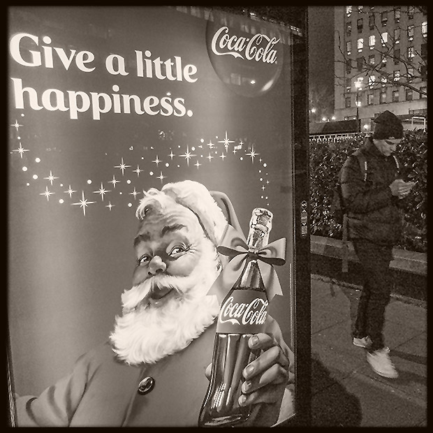 ©Neil Turner, December 2014. Pedestrian busily using his movie phone walks past a bus shelter Coca-Cola advertisement offering some seasons branding.