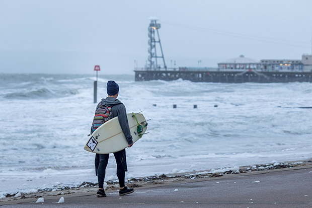 ©Neil Turner, November 2014. Surfer heads towards Bournemouth Pier as the waves get bigger during a storm.
