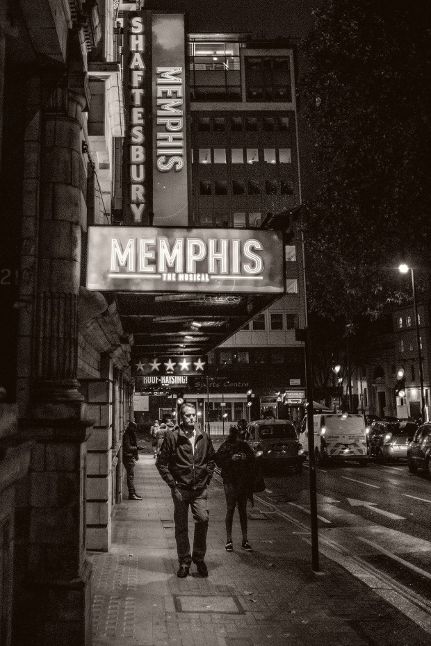 "Pedestrian passes under the ""Memphis"" banner outside a west end theatre at night. © Neil Turner November 2014."