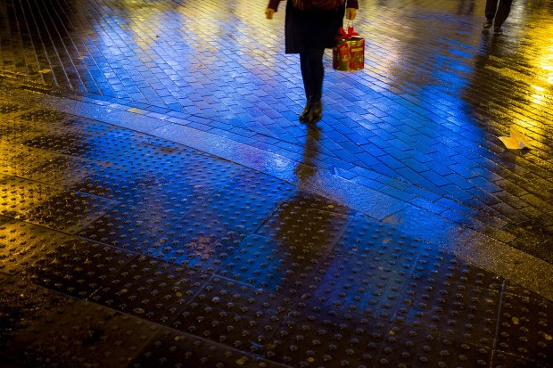 Lights from the Old Vic Theatre reflecting on wet roads near London's Waterloo station.