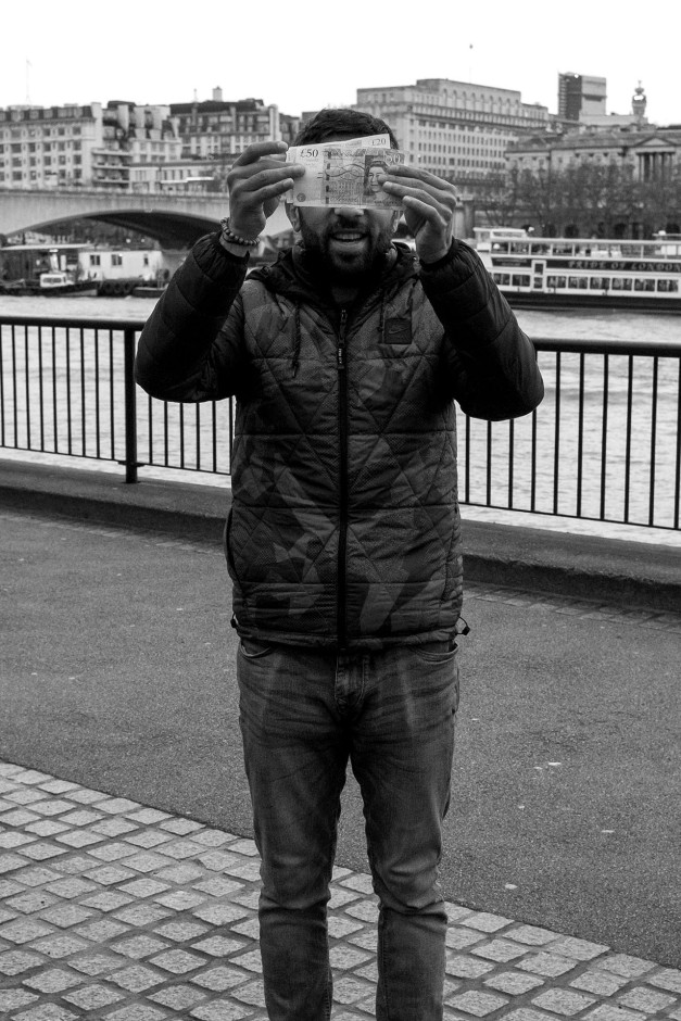 Shell game players hides his face with £50 notes on the South Bank in London. © Neil Turner, December 2015